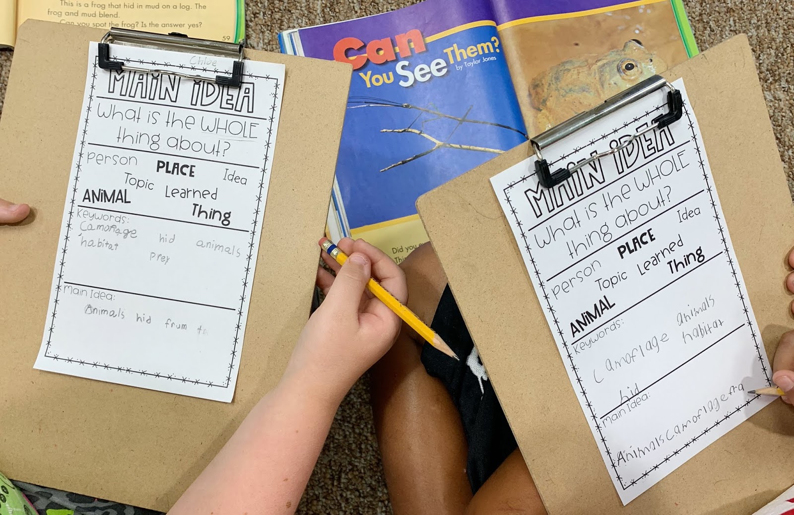 Students using a textbook to fill in their main idea mini anchor charts