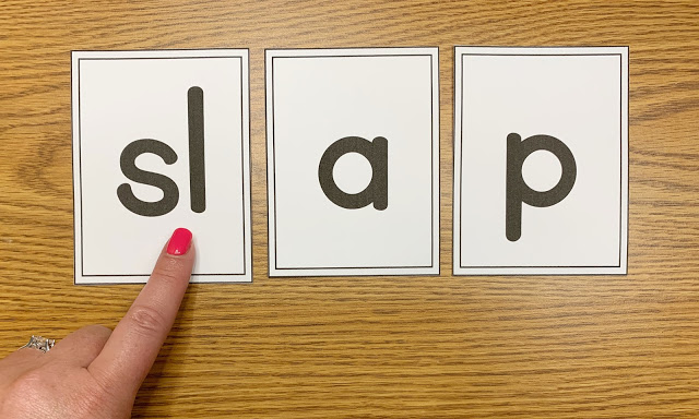 Image of a Desk with Three Cards that Spell out the Word Slap with a Finger Pointing to the SL of Slap