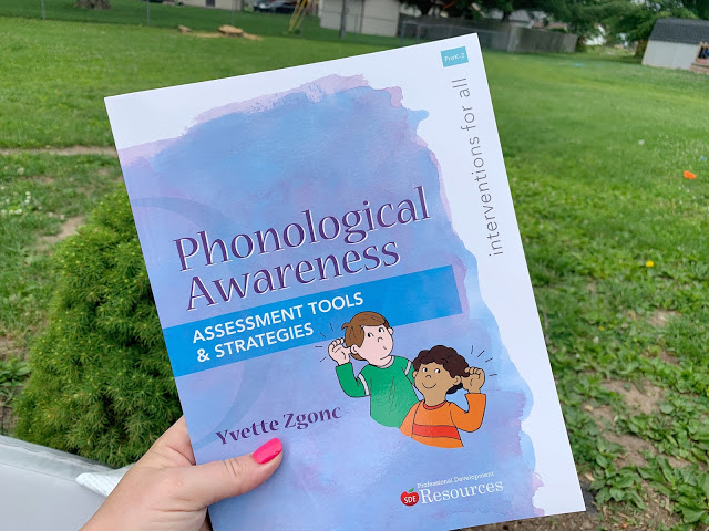 """Image of The Primary Gal Holding a Book Titled """"Phonological Awareness: Assessment Tools & Strategies"""" as her Second Choice for Professional Development Books for Special Education"""