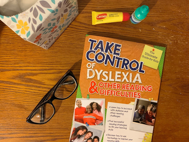 """Image of a Desk with a Kleenex Box, Glasses, Chapstick, and a Book with the Title """"Take Control of Dyslexia & Other Reading Difficulties"""""""