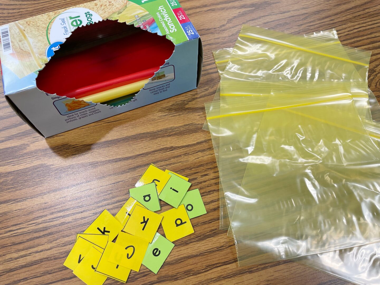 Image of Colored Sandwich Bags in a box with 5 Yellow Bags Laid on Desk with Letter Tiles used for Teaching Spelling